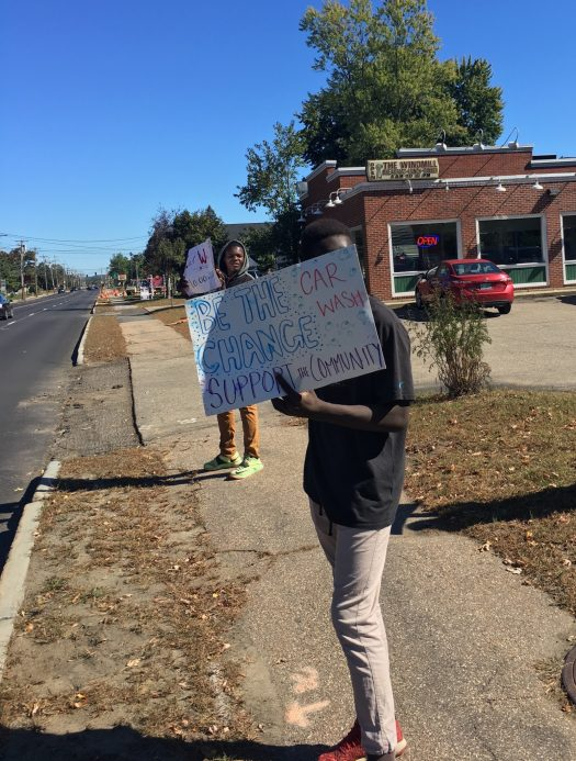 Students took turns alerting passing drivers to the car wash.