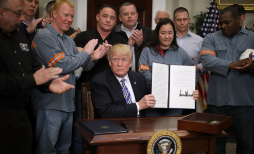 Donald Trump surrounded by steel workers after signing the tariff into law. Courtesy of Gettyimages.