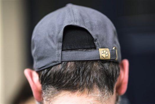 A jewish man hiding his kappah (tiny hat) with a baseball hat