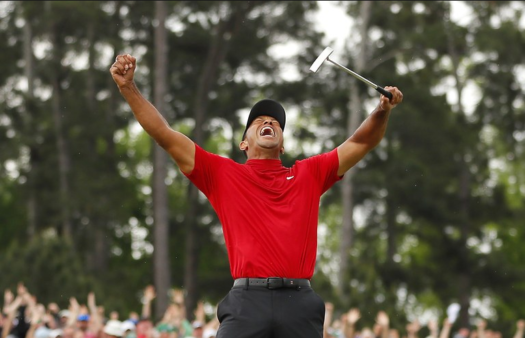 Tiger celebrating after sinking the putt to clinch the win on the 18th green at Augusta.