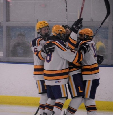 Lakewood hockey plays cheer and huddle together.
