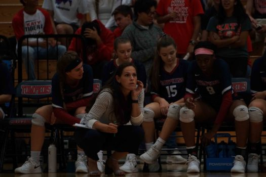 Coach Merrell focuses on watching her varsity volleyball team play during a game.