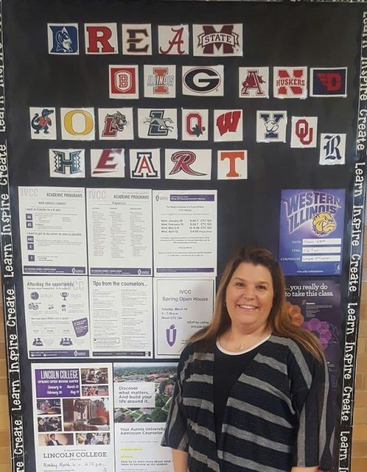 Counselor Kim Swords poses in front of the college information board