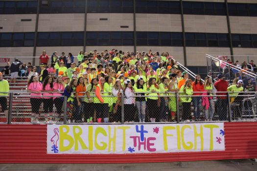 "The Superfans cheer on the football team on ""Neon Night."""
