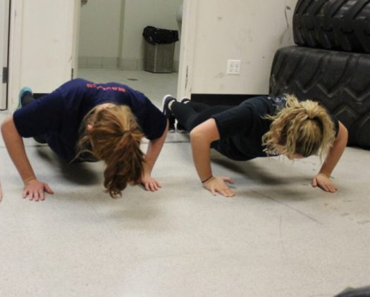 Summers and OHS graduate Elsa Kalis do push ups at the begining of their weekly training.