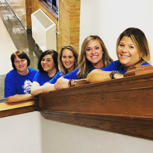 The counselors pose on the staircase in the passageway