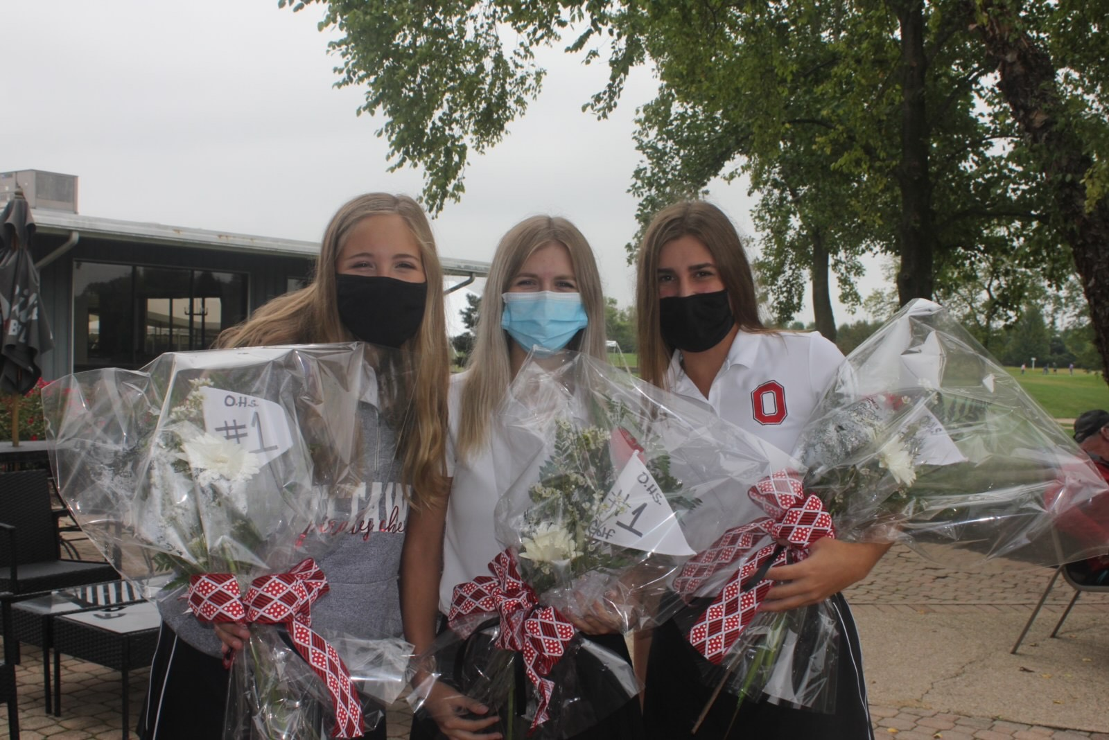 Mask on! The three seniors on the girls golf team pose for a photo at their senior night.