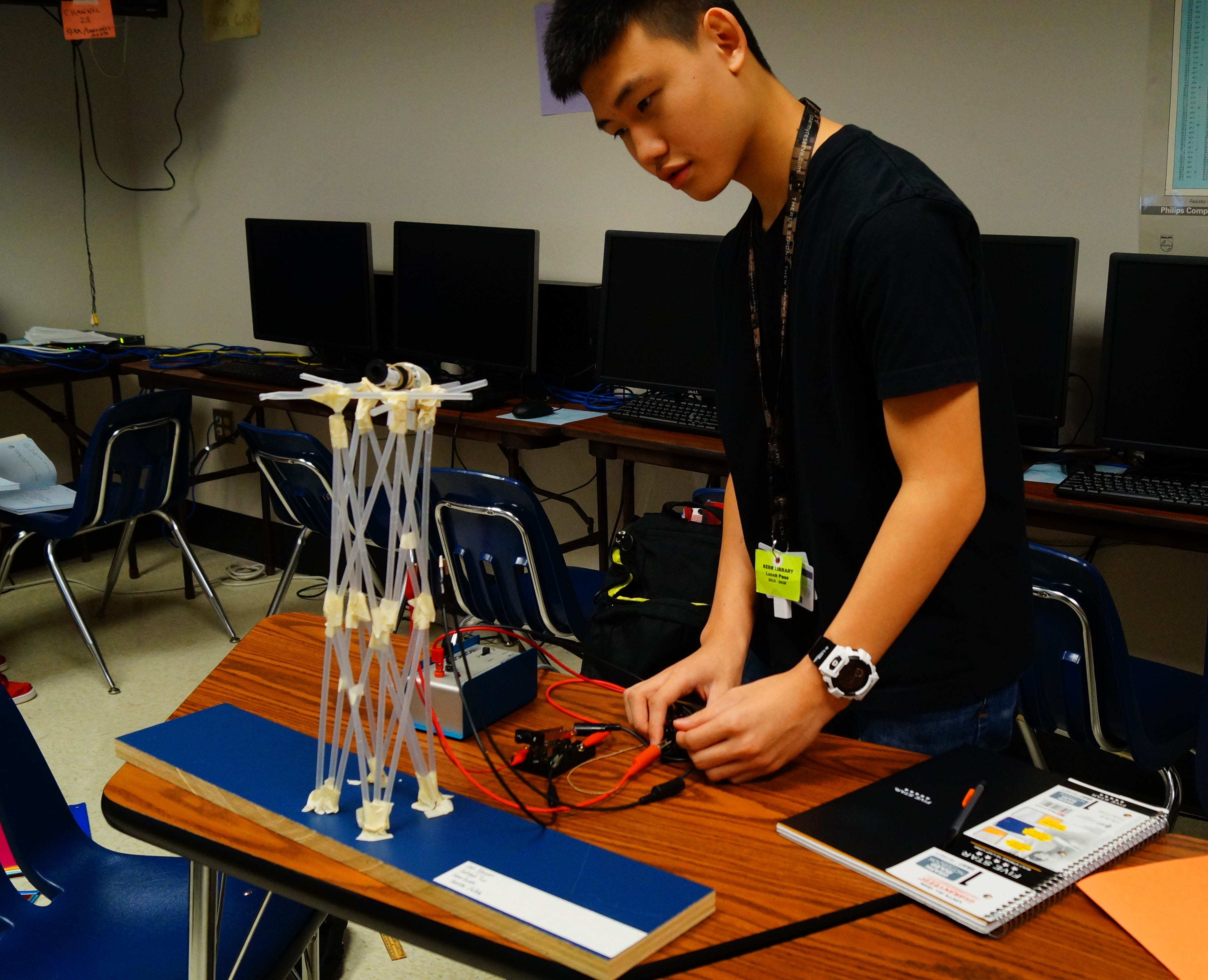 Junior Linh Nguyen tests out his elevator mechanism by varying weight, speed, and time in a project this fall.