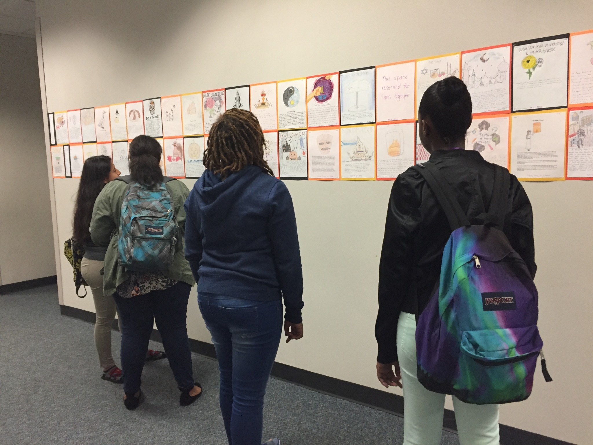 Several Freshman were critiquing each other's work that is hung up in the Social Studies Center hallway. The hung up work is based on the different Thanksgiving traditions all around the world.