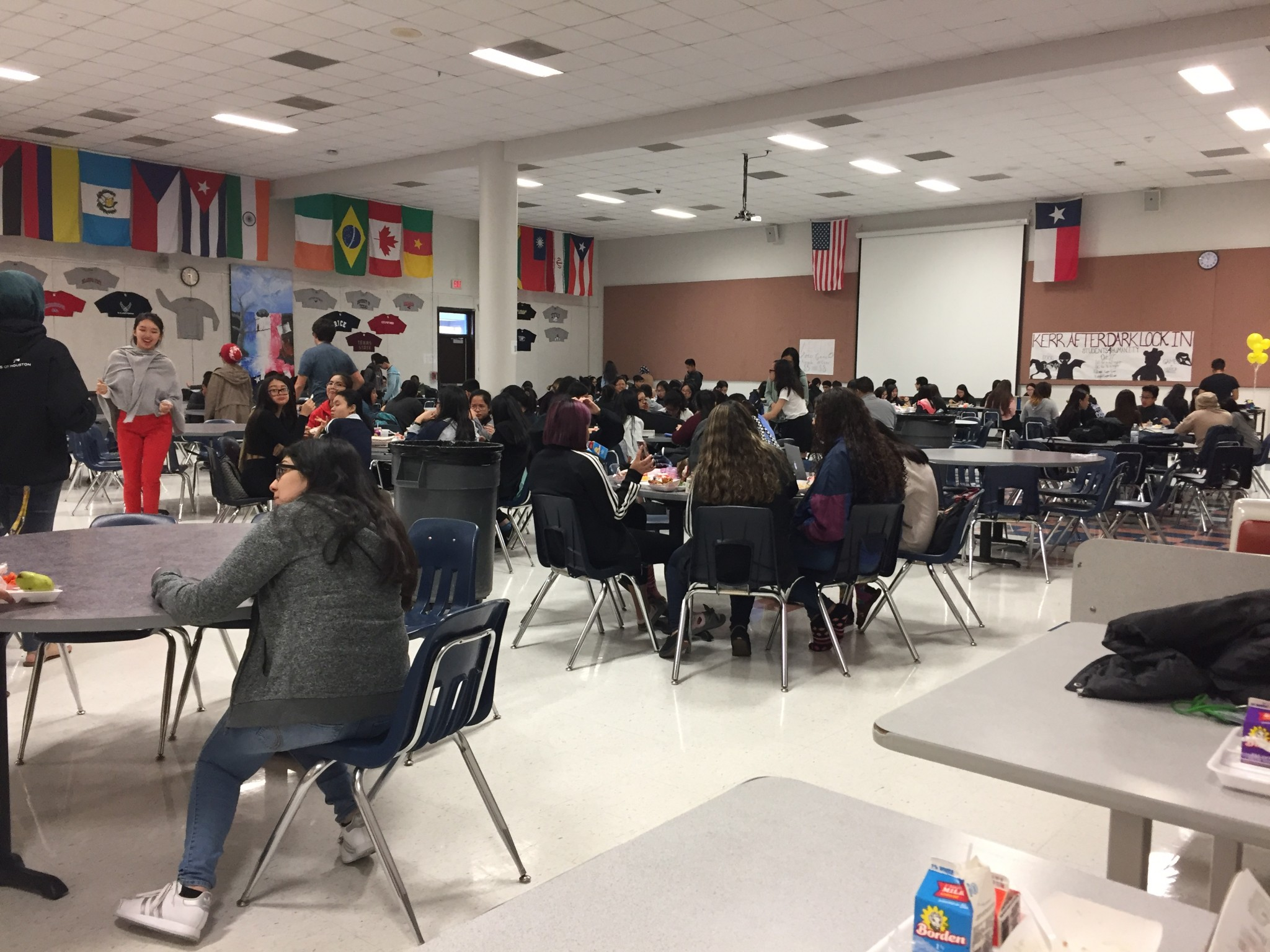 B lunch students sit together in large groups and enjoy their lunch. Various organizations are selling and promoting their purpose.