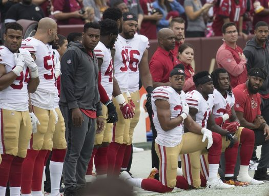 Members of the San Francisco 49ers kneel during the National Anthem to protest societal injustices.
