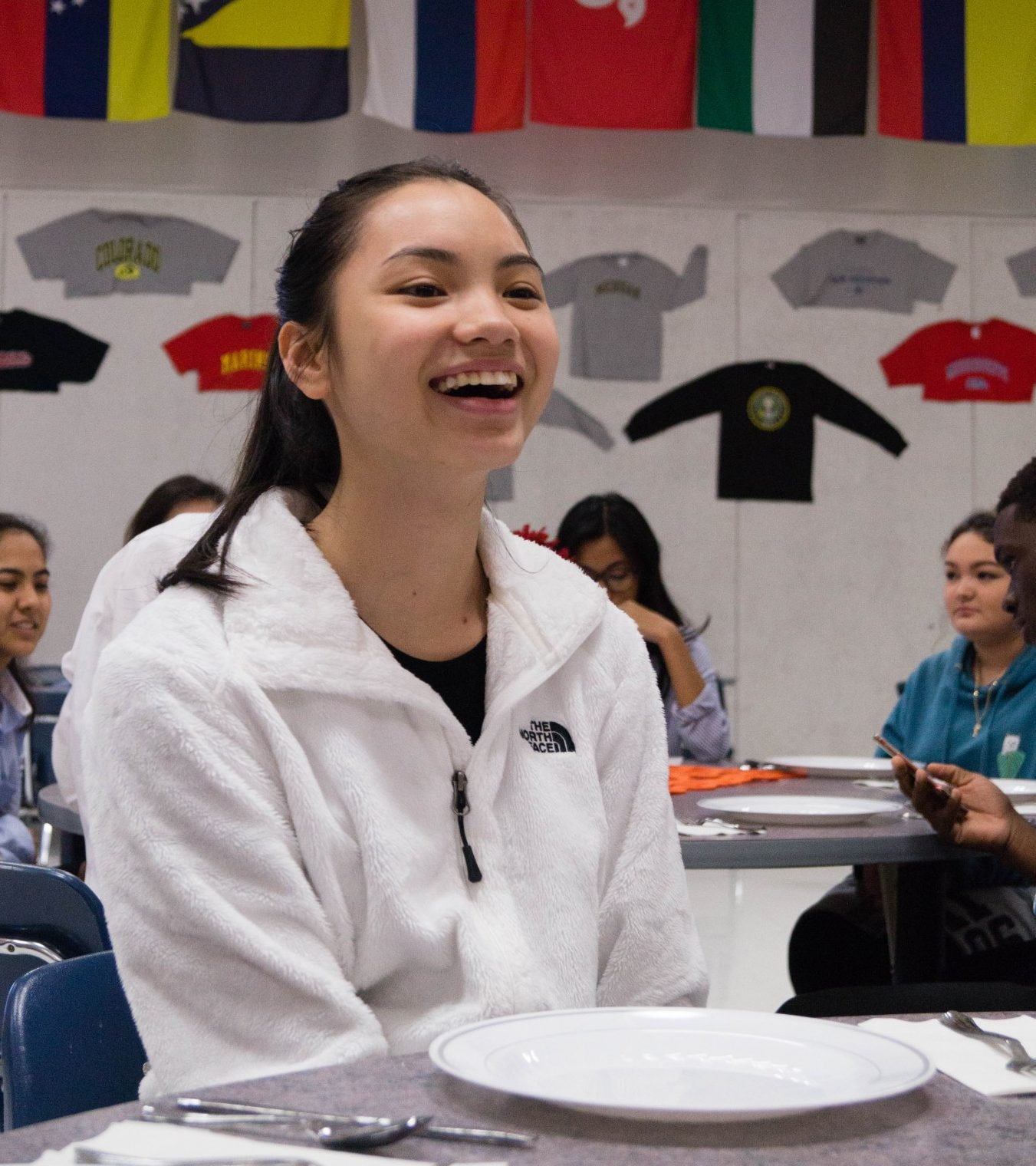 Vi Le (12) laughs at a joke made at the table as she converses with others at the FBLA Eating Workshop.