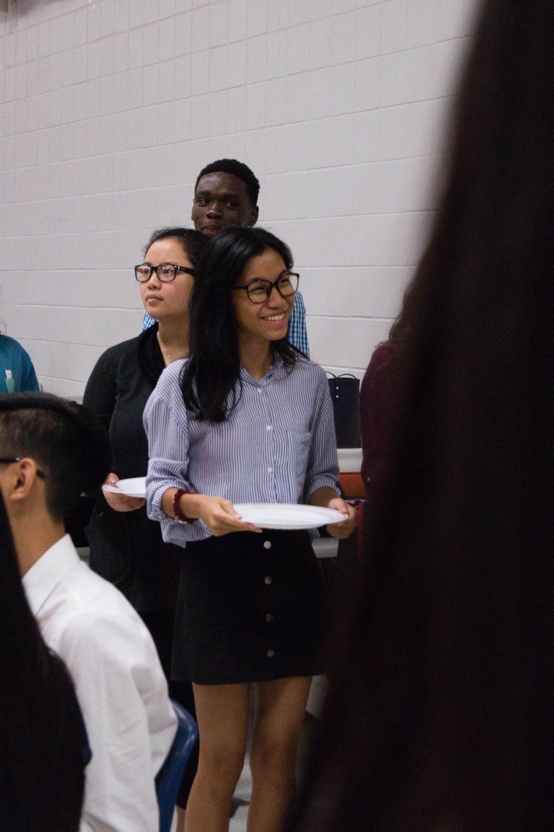 David Balogun (11), Song Nguyen (11), and Kristine Nguyen (12) impatiently wait in line for the pasta and salad for their lesson on eating etiquette.