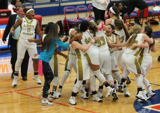 The Lady Bison celebrate their win at the end of the first game of the regional tournament.