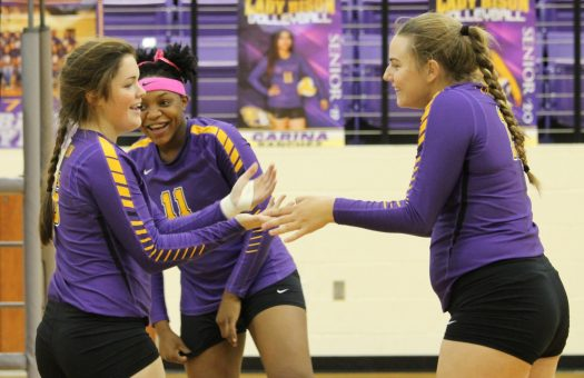 Mollie Dittmar, Melanie McGill and A'sia Bradley celebrate a point during their last district game.
