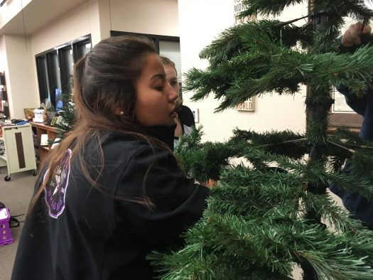 Freshman Scarlet Carrillo helps to put together the library Christmas tree.