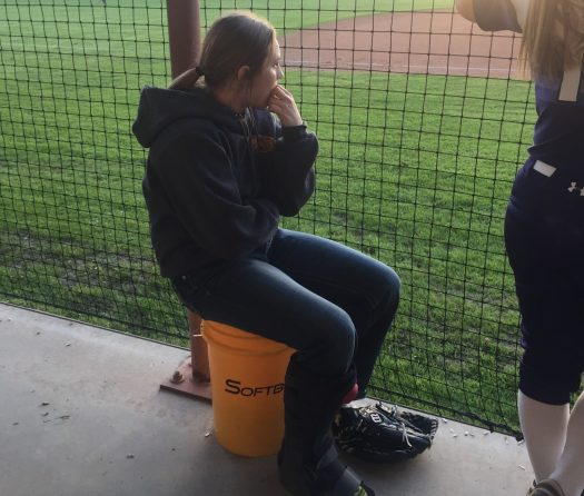 Sophomore Savannah Helmcamp watches the game from the dugout.