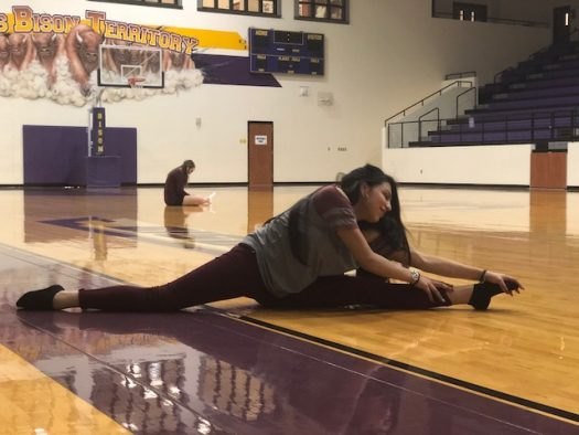 Freshman Kayla Saenz stretches before Belle practice.