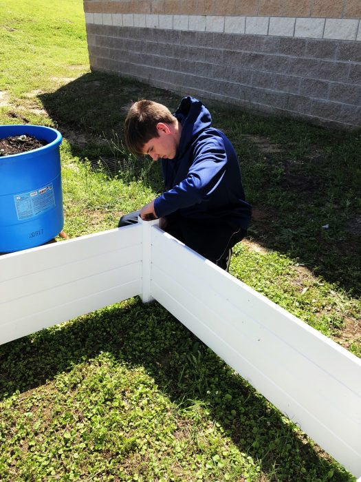 Jordan Steele works on the gardening area for the Life Skills vegetable garden.