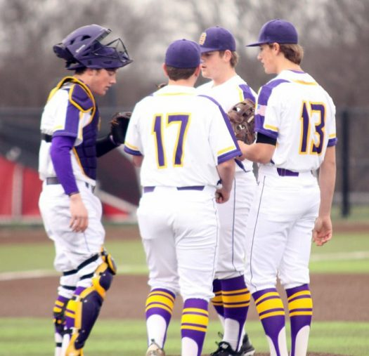 Bison baseball players confer on the mound during a game.
