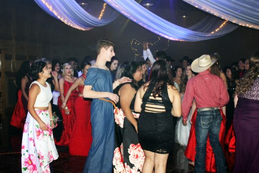 Students dance at prom before awards are announced.