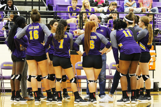 The volleyball team listens to coach Daryl Skelton during a time out.