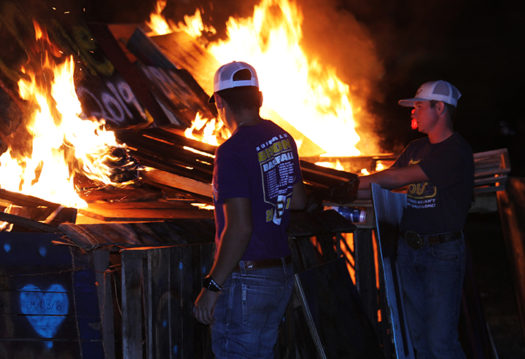 Seniors Peyton Graves and Riley Webb light the bonfire.