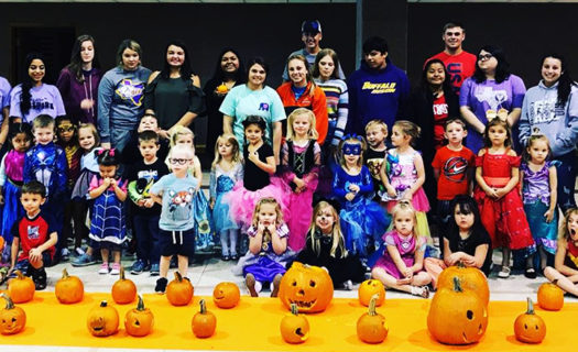 FCCLA members and preschool students show off their carved pumpkins.