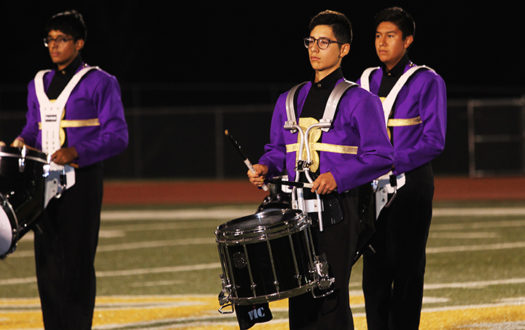 Freshman Eddie Aguillar performs with the Brigade at halftime.