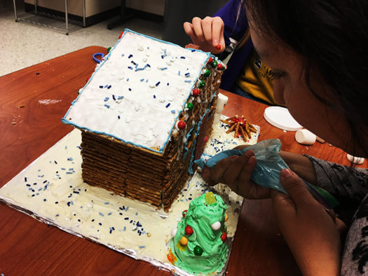 Senior Stefani Trejo decorates her gingerbread house for the Belle contest.