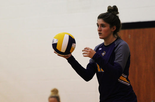 Sophomore Justice Herrera gets set to serve during a volleyball match.