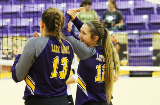 Seniors Mollie Dittmar and Rylee Reeves share a grin during a volleyball game.