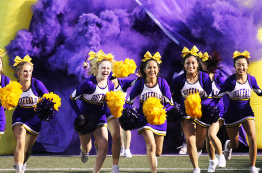 The cheerleaders lead the way as the varsity team bursts from the tunnel before the Homecoming game.
