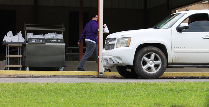 Brittney Ansley delivers a meal to a student at lunchtime on Monday.