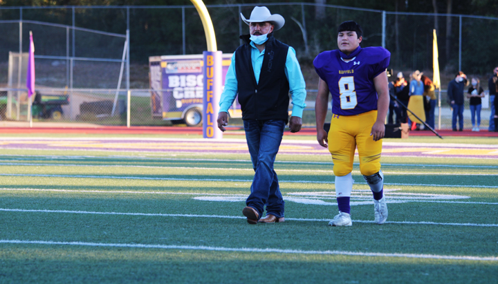 Senior Benito Avila and his father head to the 50-yard line during Senior Walk.