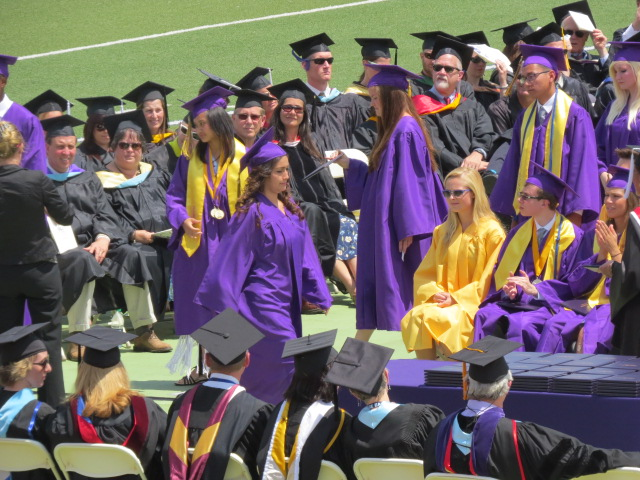 Graduates walk to receive their diplomas