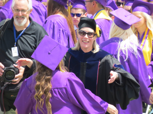 Dr. Amy Oaks reaches out to hug a graduate