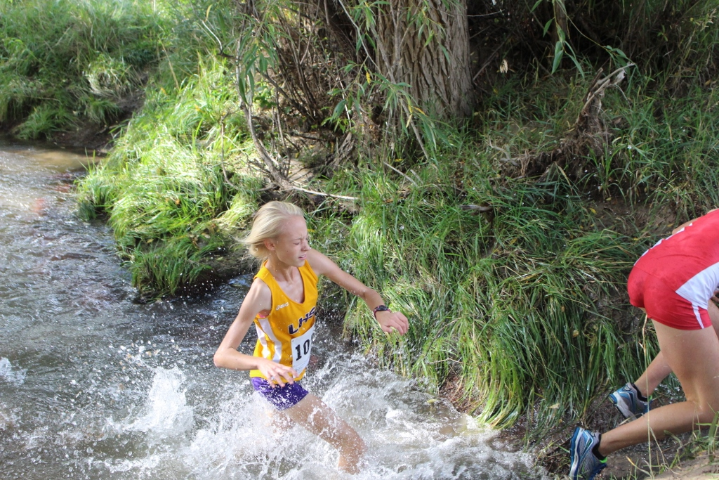 Freshman Addie Icken spalshes through a water crossing at the LHS Invitational