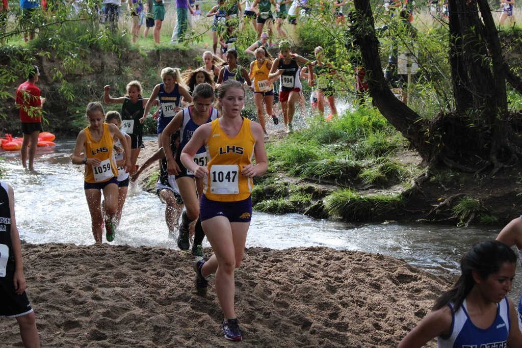 Sophomore Ashby Bell leads a group of runners into the water crossing
