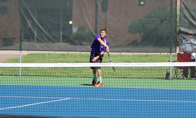 Seth Goldstein serves during regional tennis match.