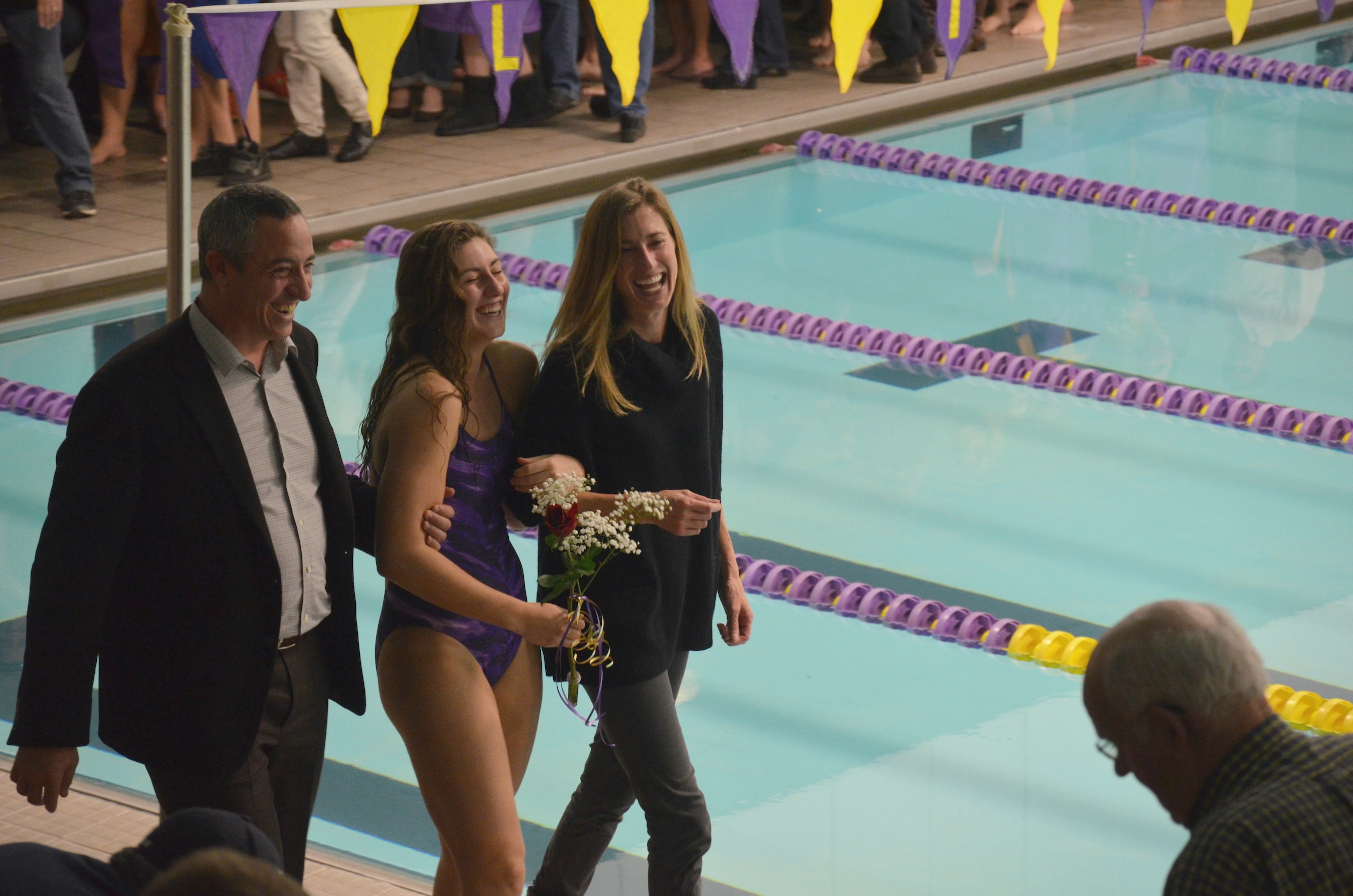 Senior Emily Burch and her parents walk together to receive her Senior Night recognition