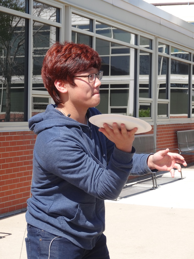 "Wearing his concentration face, sophomore Chris Hong attempts to throw a whipped cream ""pie"" into the face of a teacher."
