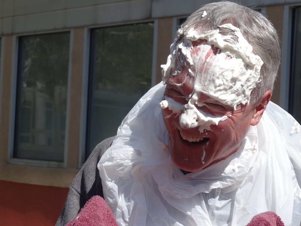 Social studies teacher Greg Klein laughs off the direct hit that he got from a whipped cream pie. Klein received the most votes out of all the administrative staff.