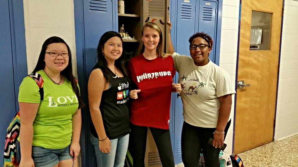 Students pose by lockers dressed in shirts from China, Vietnam, Germany and Morocco.