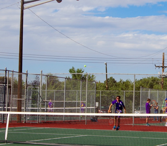 Two singles player Zach Fox serves the ball.