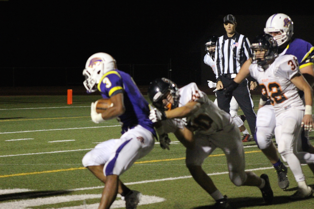Senior Noah McGhee surges forward, trying to break free of the Wildcat player making a tackle.