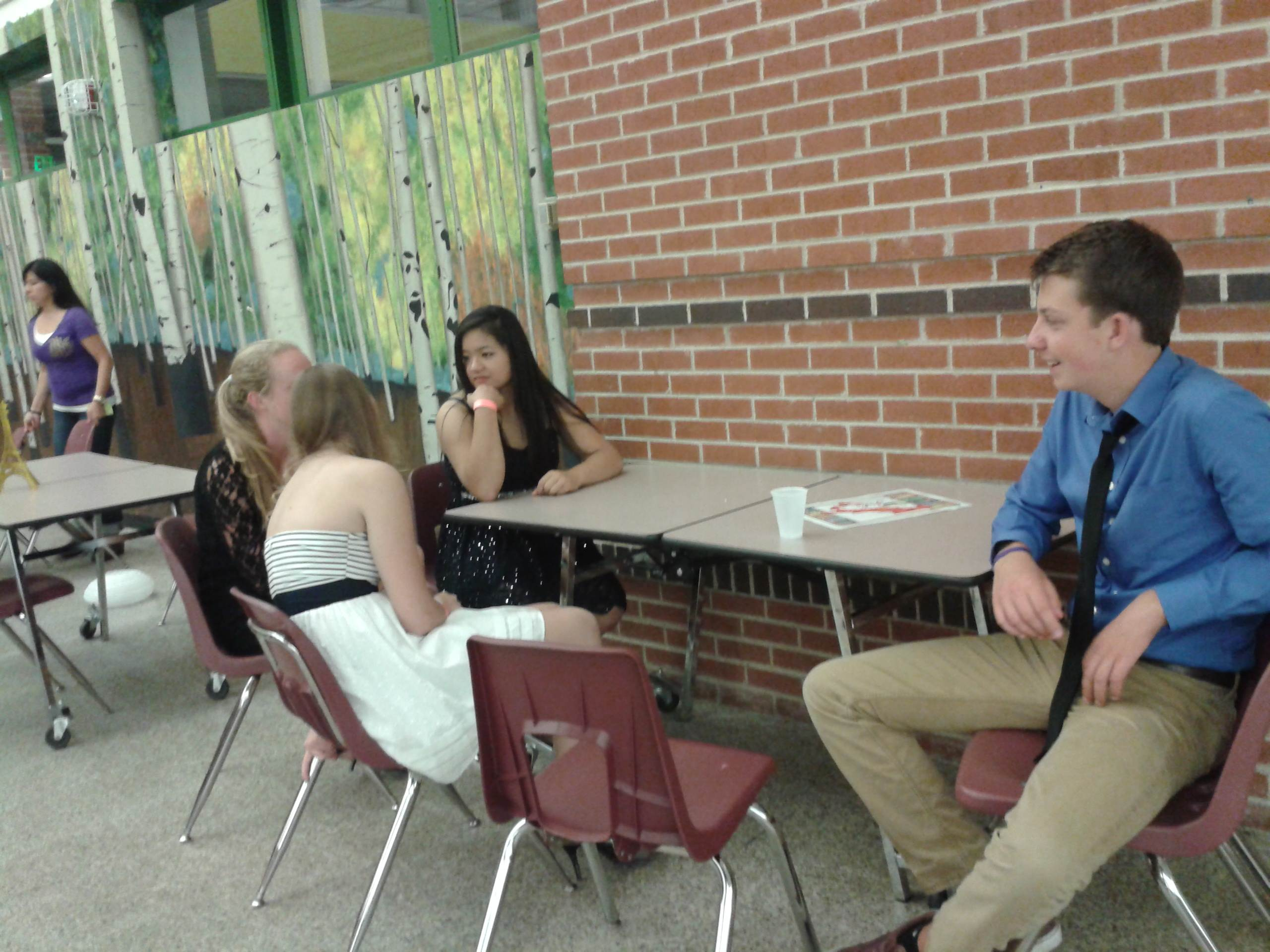 A group of seniors have a casual conversation, while enjoying the quiet of the Cafeteria.