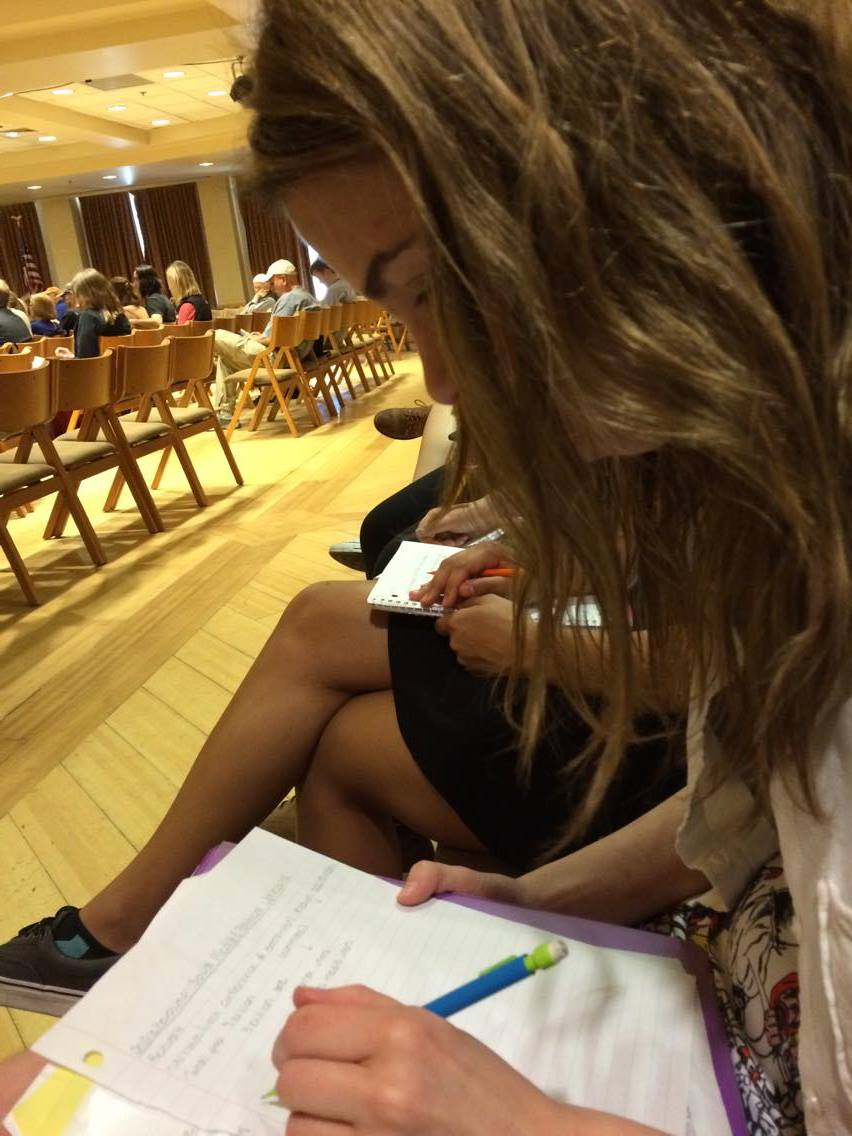 Junior Lizzie Lumley takes notes in a seminar hall at CU