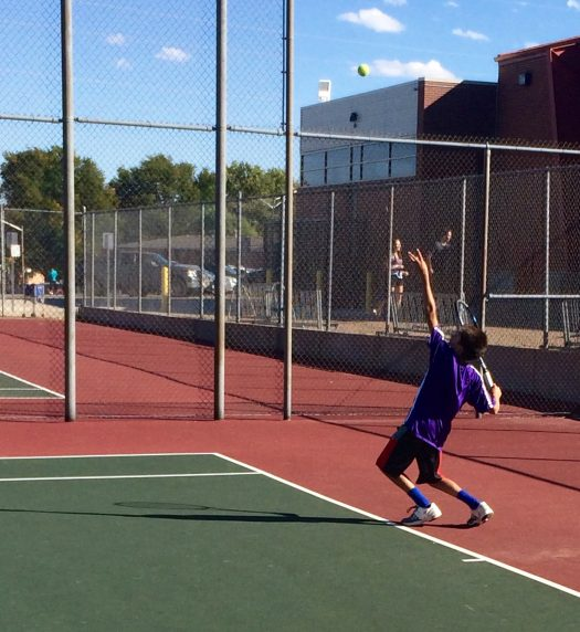 Freshman Jeanloup Auzias tosses the ball in the air on a serve.