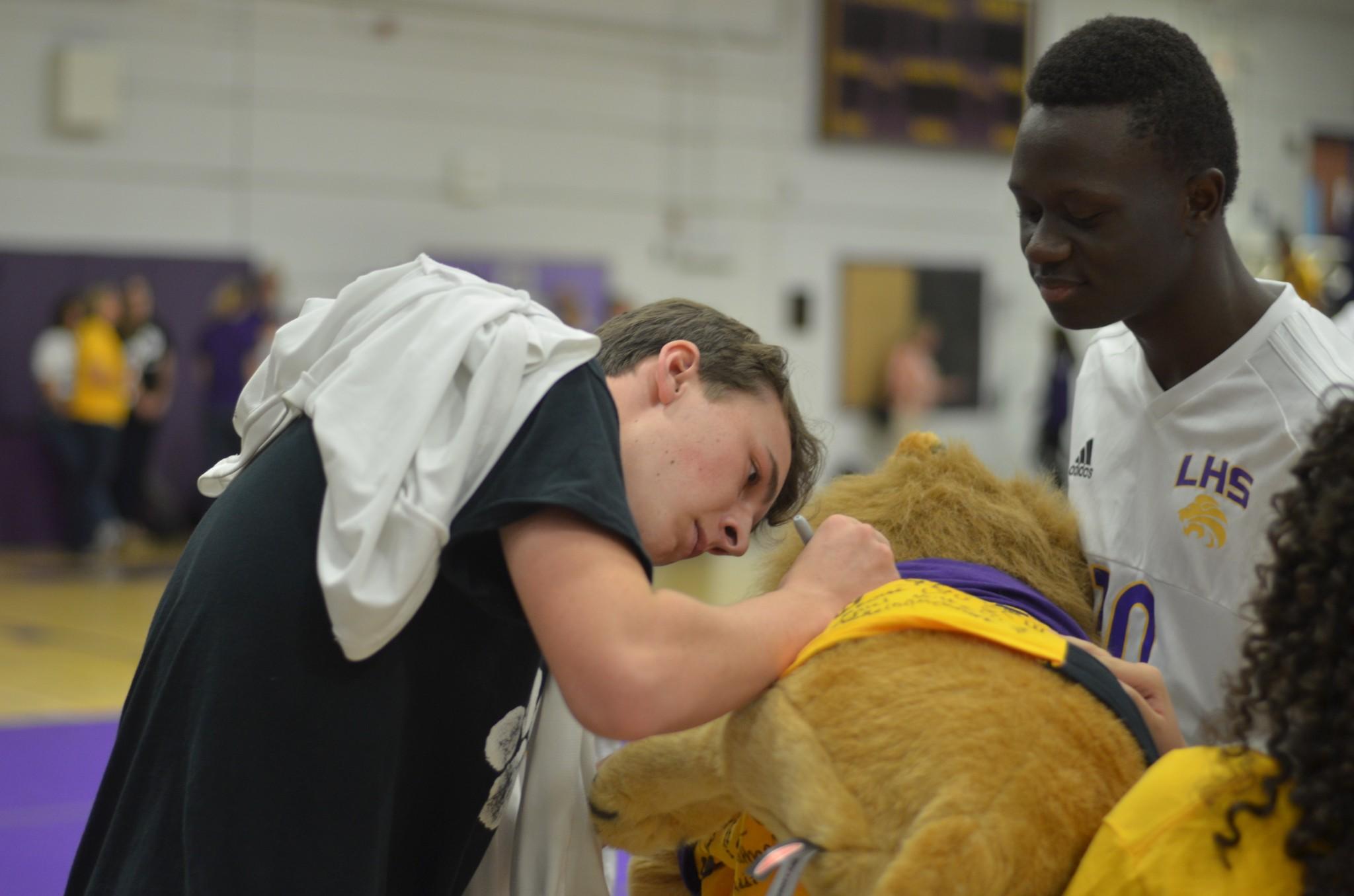 Junior Zach Maguire signs the spirit lion
